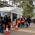 People-wait-in-line-outside-a-coronavirus-disease-COVID-19-vaccination-centre-at-Sydney-Olympic-Park-in-Sydney