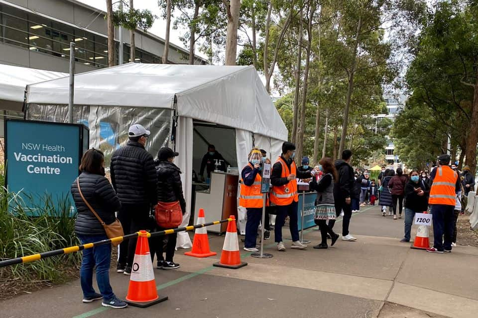 People wait in line outside a coronavirus disease (COVID-19) vaccination centre at Sydney Olympic Park in Sydney